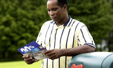 African American man getting mail from mailbox