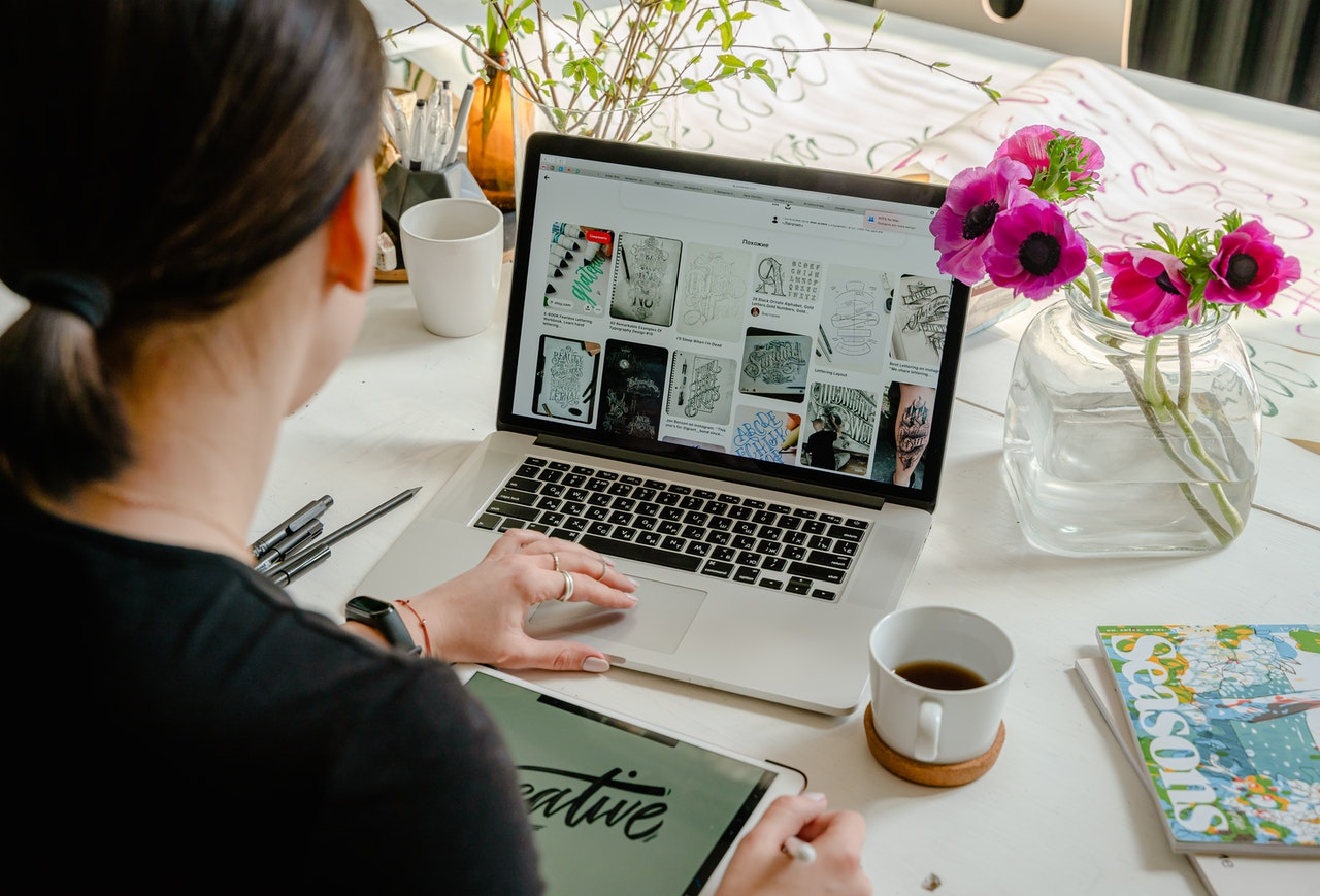 woman designing flyer on laptop