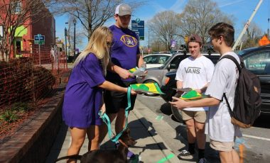 children handing out school event flyer